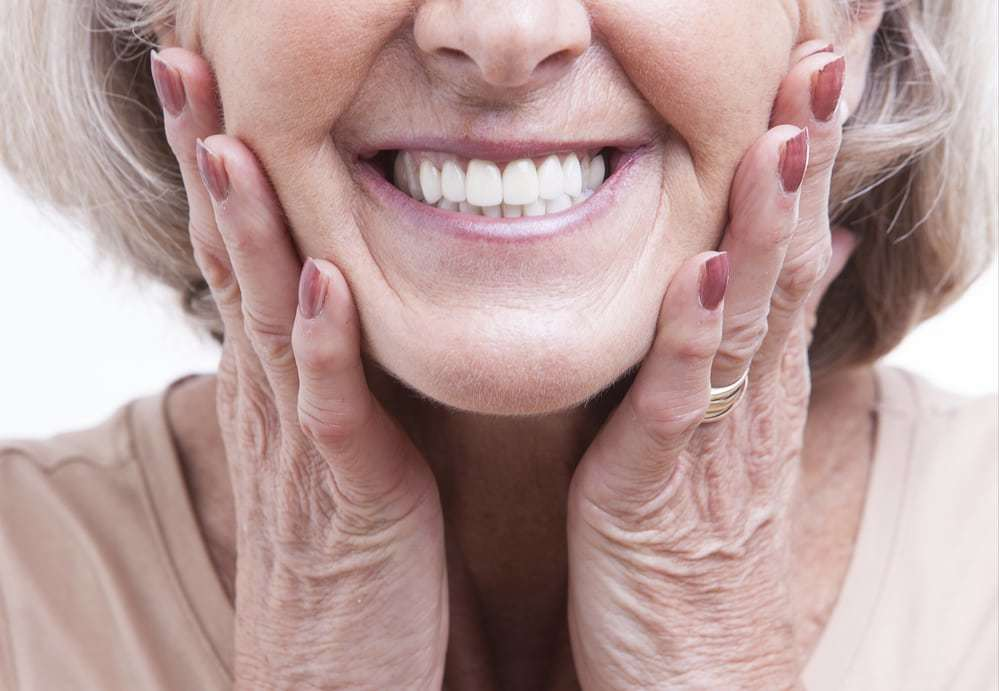 senior woman with dentures smiling